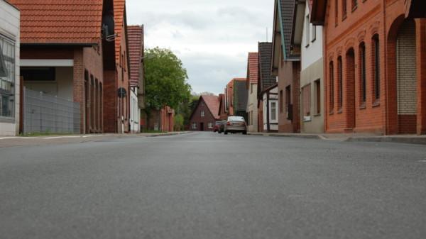 Eine asphaltierte Straße in einem Ortskern. Rechts und Links sind Häuserreihen erkennbar.